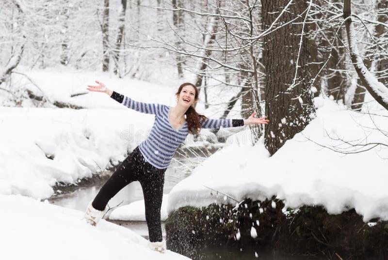 Den unga gravida kvinnan som går i ett snöig, parkerar arkivfoto