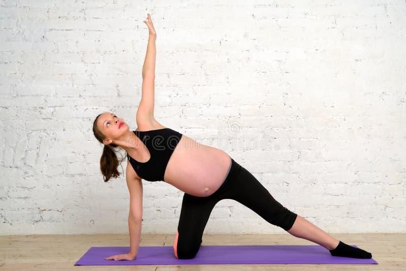 Den unga gravida kvinnan som gör sträckning, övar på matt yoga royaltyfria bilder