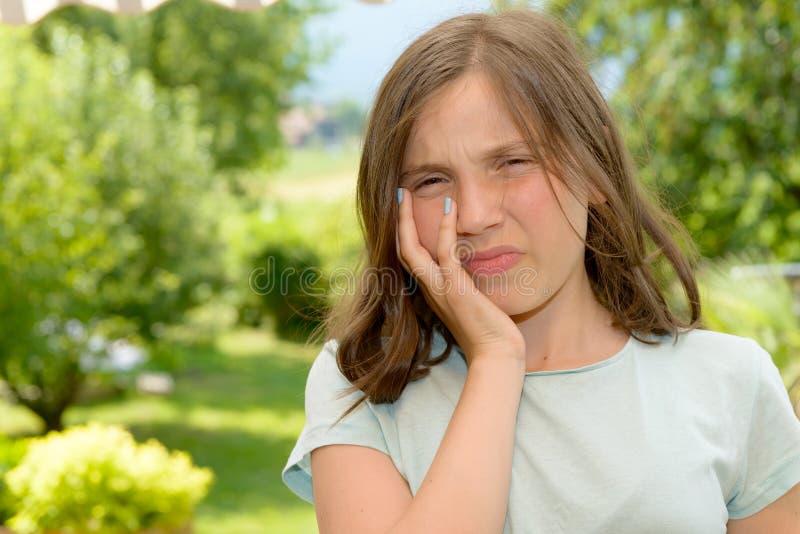 Den unga gulliga barnflickan har en tandvärk royaltyfria bilder