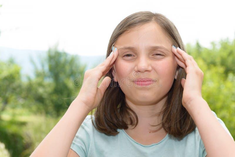 Den unga gulliga Caucasian flickan har en huvudvärk royaltyfri bild