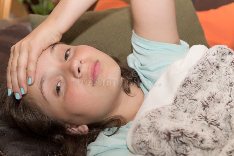 Den unga gulliga Caucasian flickan har en huvudvärk royaltyfri foto