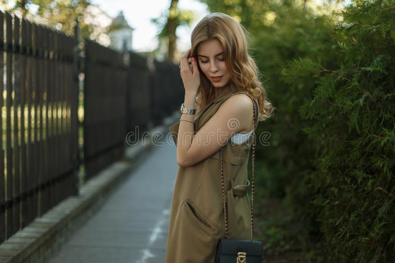 Den unga gulliga charmiga kvinnan i en trendig sommar tilldelar en stilfull vit T-tröja som poserar i, parkerar på en solig dag royaltyfri foto