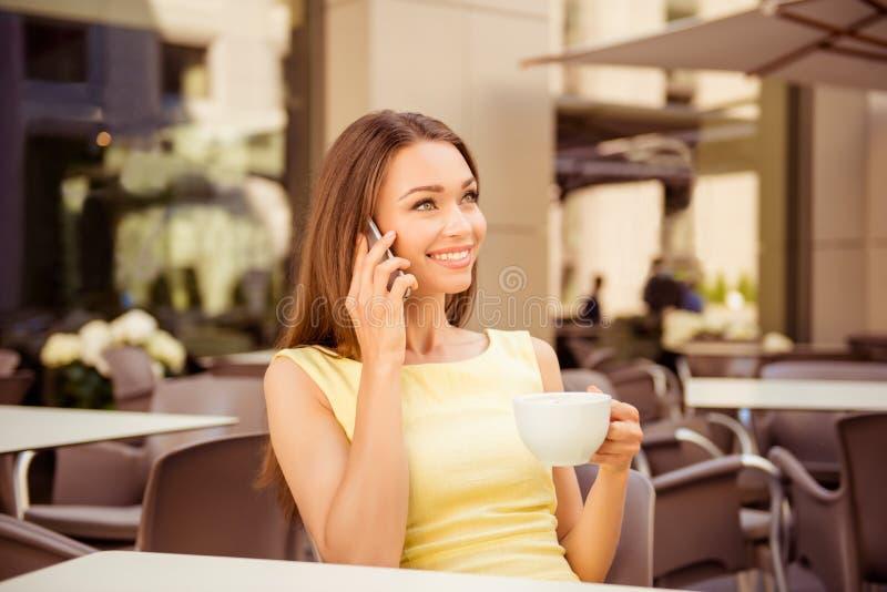 Den unga gulliga damen talar på hennes smarta telefon, medan ha kaffe i terrassen för öppen luft av kafét Hon är i den eleganta d royaltyfri foto