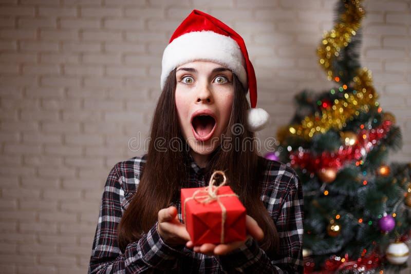 Den unga gulliga förvånade upphetsade kvinnan i jultomtenlock förbluffas av ett p arkivbild