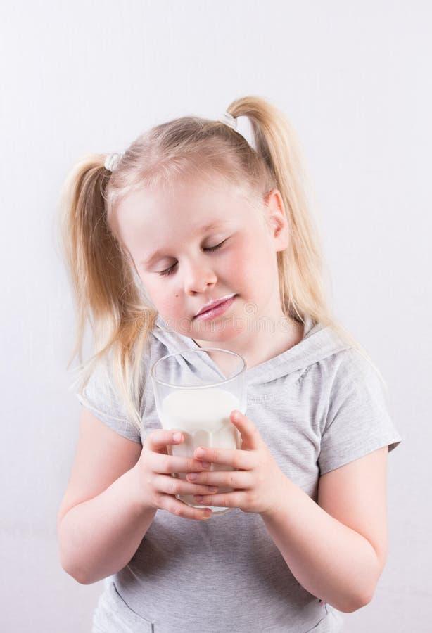Den unga gulliga lilla blonda flickan i den vita t-skjortan som ler och rymmer exponeringsglas av, mjölkar arkivfoto