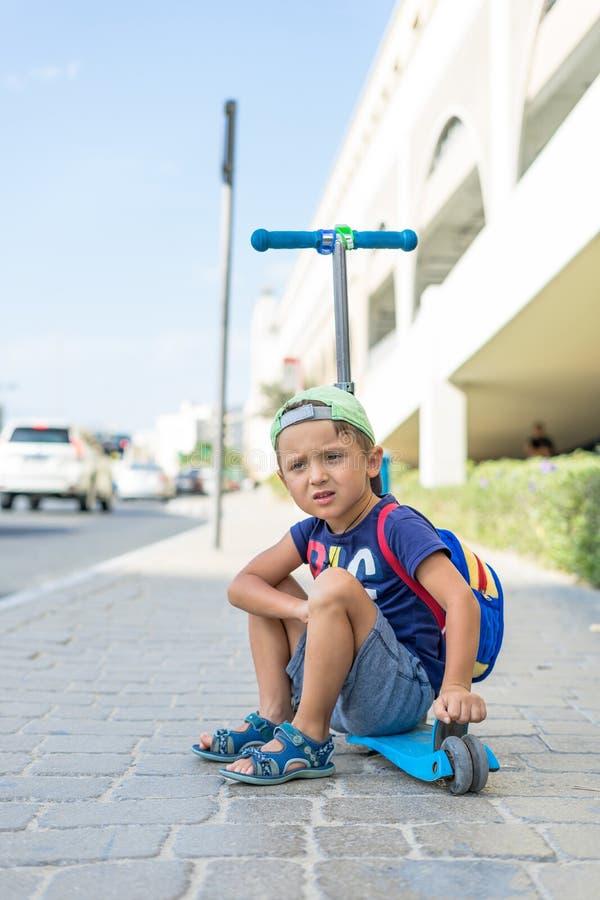 Den unga gulliga pojken sitter på sparksparkcykeln på en hållplats nära emiratgallerian i Dubai som väntar på bussen Enig arabisk arkivbilder