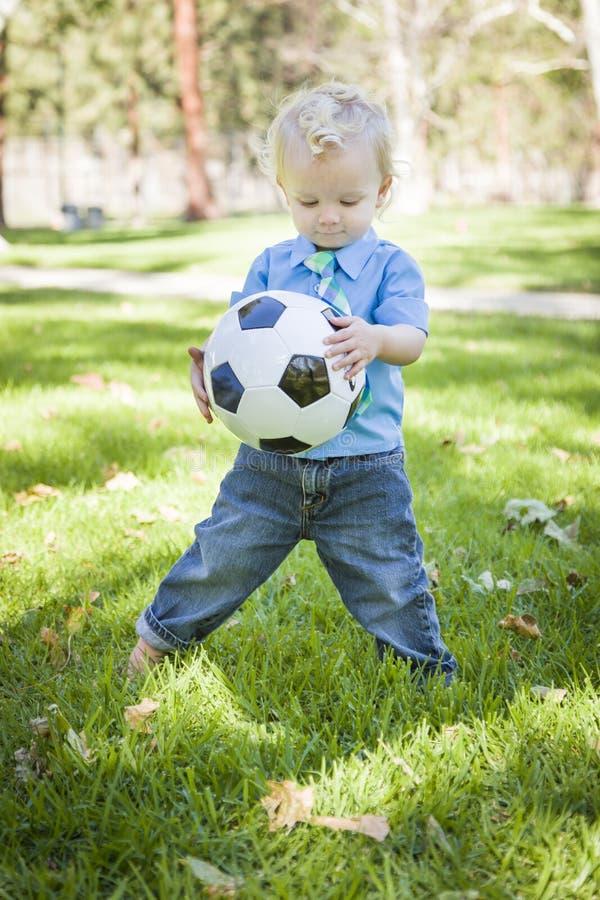 Den unga gulliga pojken som spelar med fotbollbollen parkerar in royaltyfria foton