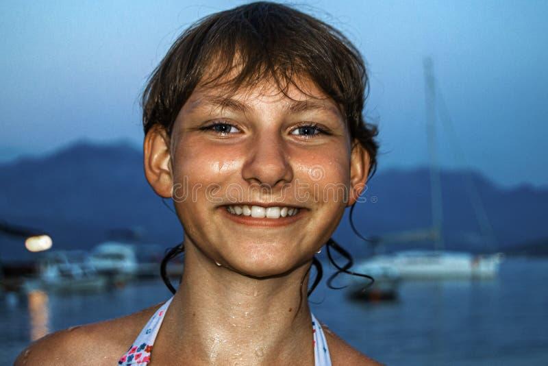 Den unga gulliga tonåriga flickan kom precis ut ur havet med droppar för ett lyckligt leende och vattenpå hennes framsida arkivfoton