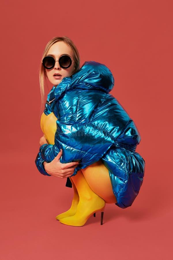 Den unga gulliga trevliga blonda flickan i blått omslag sitter i en foster- position i studio för kameran, röd bakgrund Slapp fok fotografering för bildbyråer