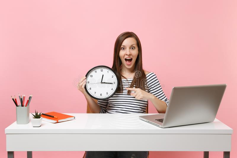 Den unga häpna kvinnan som pekar pekfingret på den runda ringklockan, sitter arbete på det vita skrivbordet med den moderna PCbär royaltyfri foto