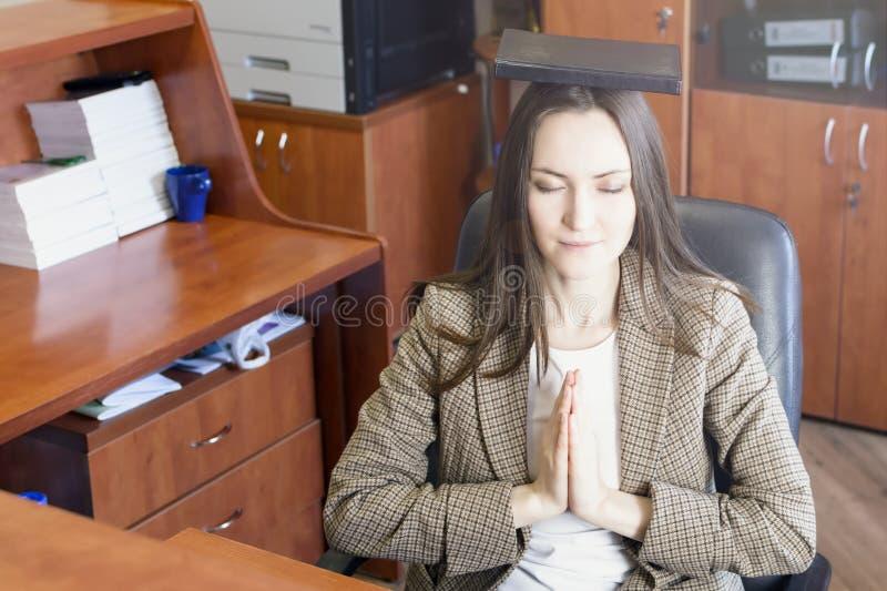 Den unga härliga affärskvinnan mediterar på tabellen i regeringsställning royaltyfri foto