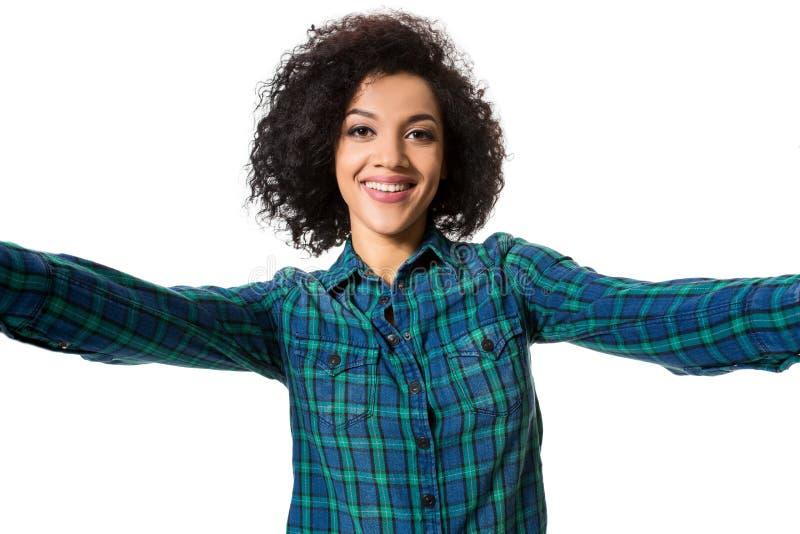 Den unga härliga afrikansk amerikankvinnan gör själv mot den vita bakgrunden i studio royaltyfri fotografi