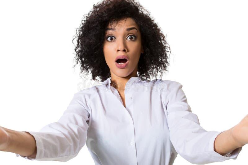 Den unga härliga afrikansk amerikankvinnan gör själv mot den vita bakgrunden i studio arkivfoto