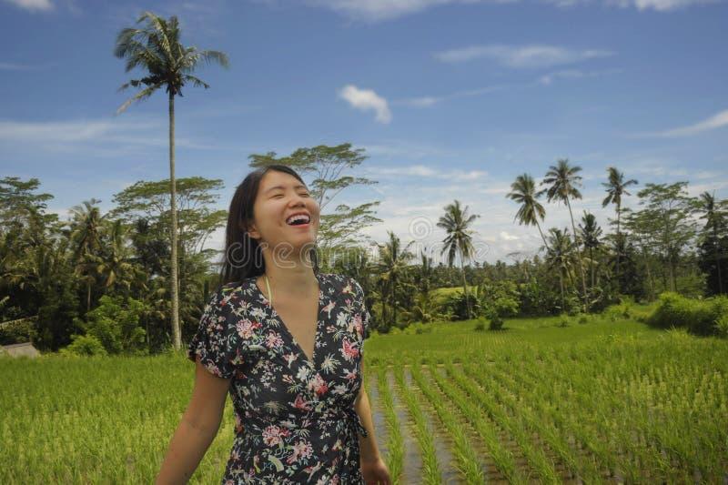 Den unga härliga asiatiska kinesiska turist- undersökande djungeln och risfältet vadderar område i Bali Indonesien den kopplade a royaltyfri bild