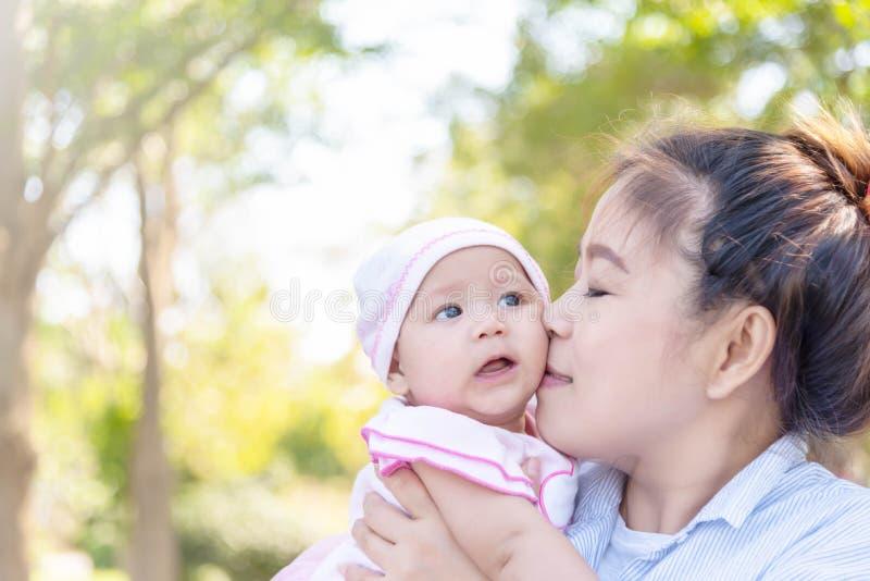 Den unga härliga asiatiska modern som kysser henne behandla som ett barn lite, 4 månader flicka Familj; moder och dotter som har  arkivbild