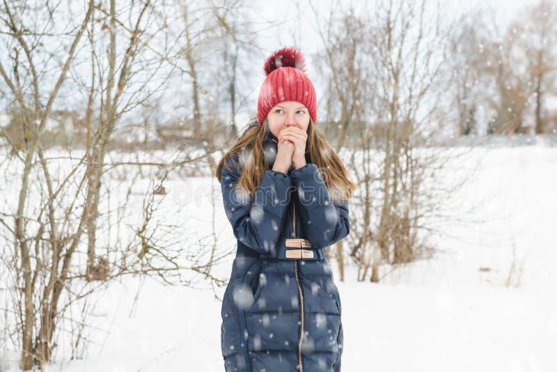 Den unga härliga blonda flickan andas på hennes händer för att värme dem i parkerar under mjuk fluffig snö royaltyfri foto