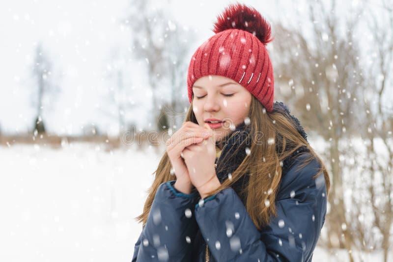 Den unga härliga blonda flickan med stängda ögon andas på hennes händer för att värme dem i parkerar under mjuk fluffig snö arkivfoton