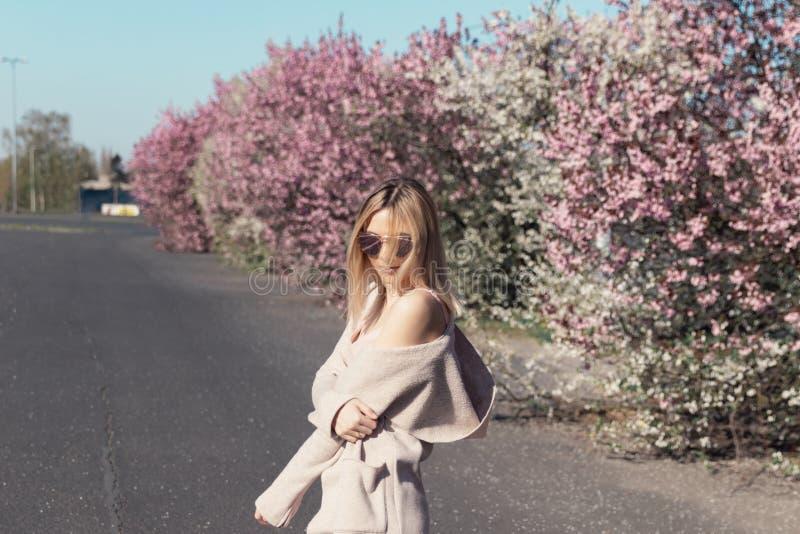 Den unga härliga blonda flickan står i parkeringsplatsen arkivfoto
