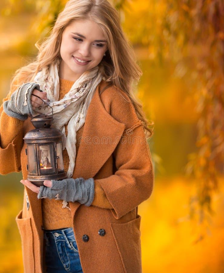 Den unga härliga blondiekvinnan i hösten parkerar royaltyfri bild