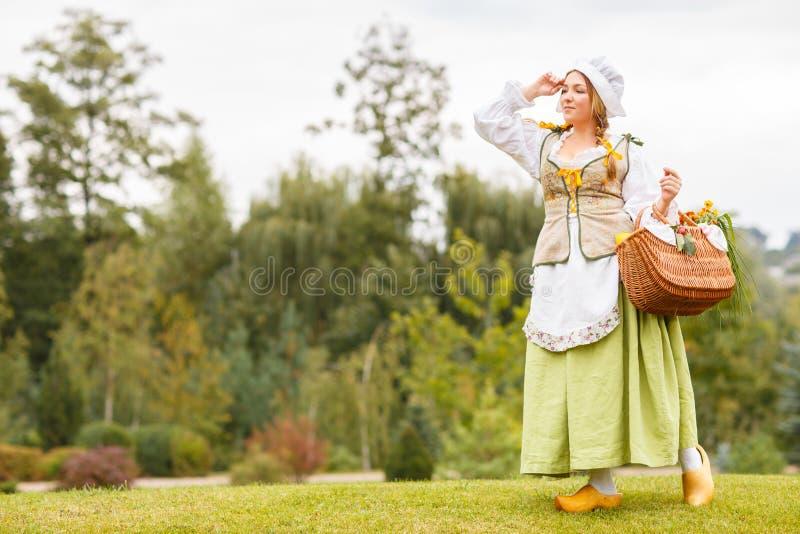 Den unga härliga bondaktiga kvinnan med en bukett av solrosor i handväska eller korg ser långt borta fotografering för bildbyråer