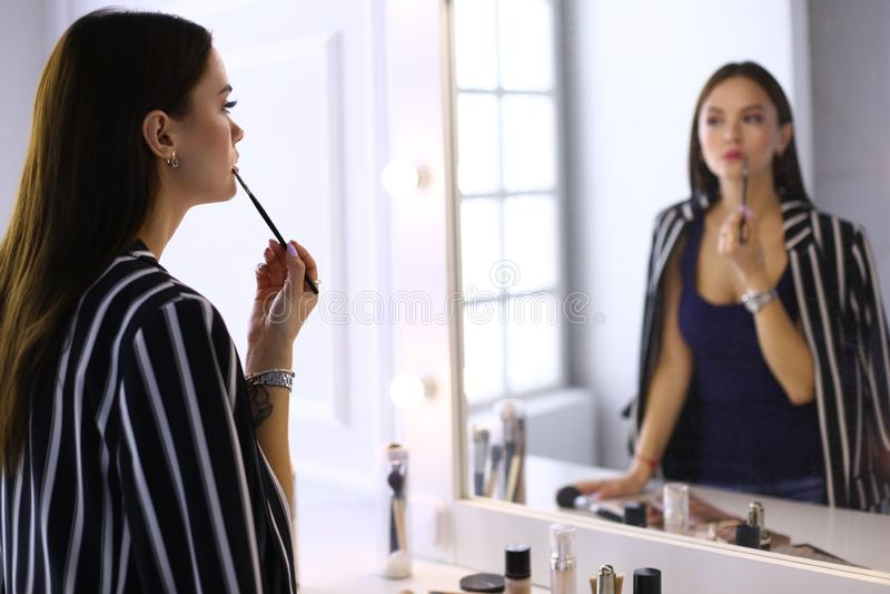 Den unga härliga brunettflickan målar hennes kanter som ser reflexion i en spegel royaltyfria bilder