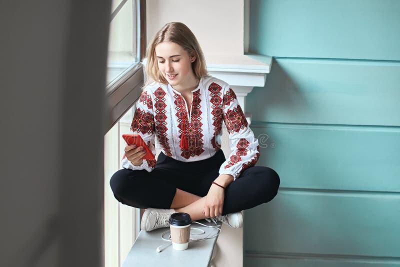 Den unga härliga caucasian flickastudenten som bär en vyshyvanka, en traditionell ukrainare broderad skjorta, kontrollerar henne fotografering för bildbyråer