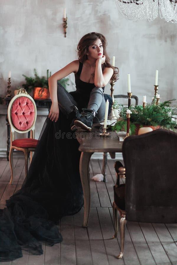 Den unga härliga damen i aftonklänning i vindinre sitter på tabellen med stearinljus och granris royaltyfria foton