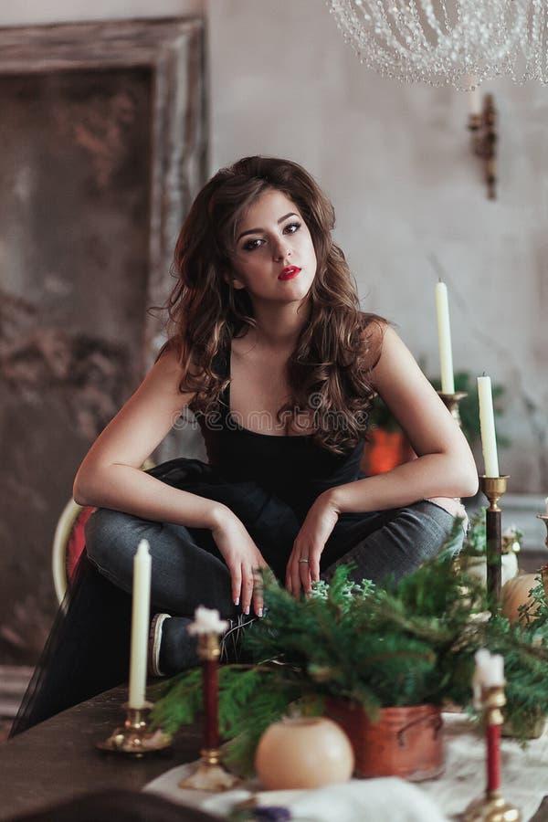 Den unga härliga damen i aftonklänning i vindinre sitter på tabellen med stearinljus och granris arkivbild