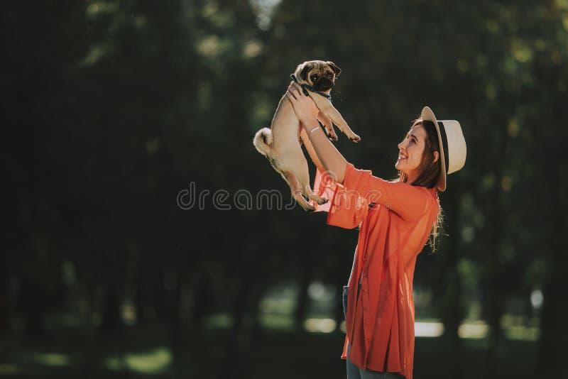 Den unga härliga damen rymmer hans trevliga husdjur royaltyfri bild