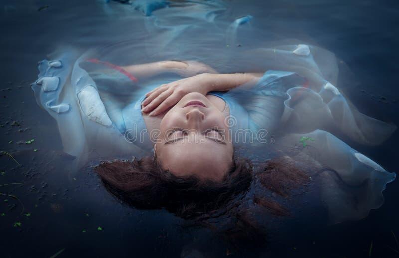 Den unga härliga drunknade kvinnan i blått klär att ligga i vattnet royaltyfri bild