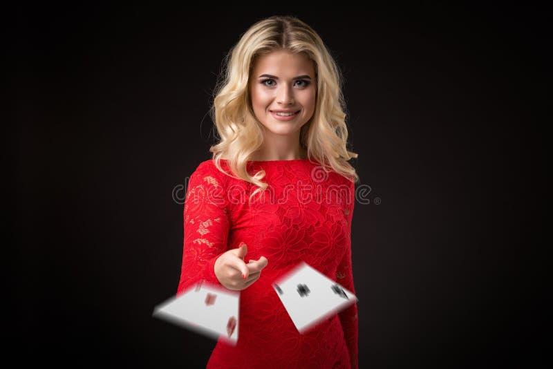Den unga härliga emotionella kvinnan kastar kort på en svart bakgrund i studion poker royaltyfri bild