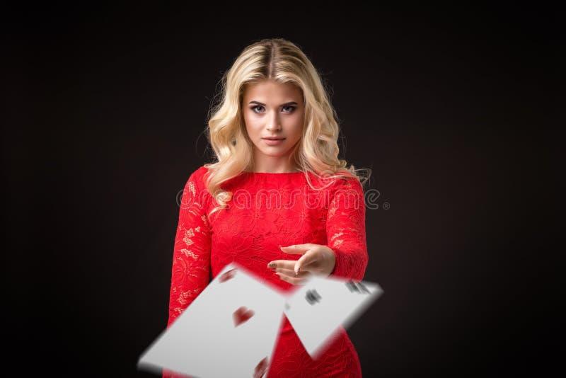 Den unga härliga emotionella kvinnan kastar kort på en svart bakgrund i studion poker arkivbilder