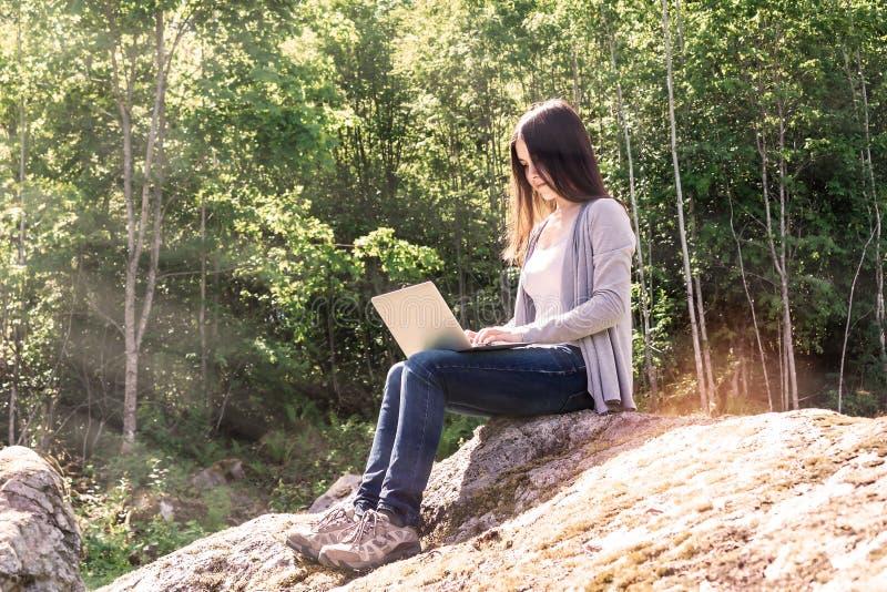 Den unga härliga flickan arbetar på en bärbar dator, medan sitta på ett stort, vaggar i det frilans- begreppet för skogen arkivfoton
