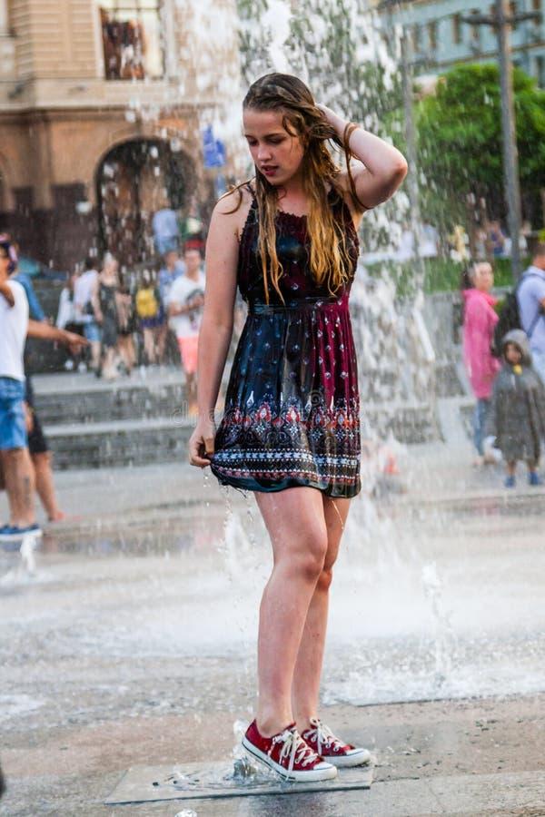 Den unga härliga flickan dansar i en springbrunn fotografering för bildbyråer