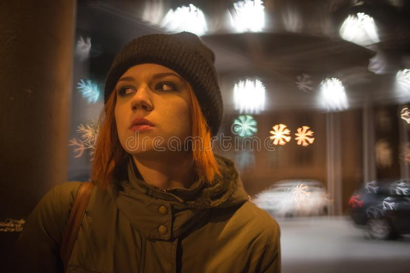 Den unga härliga flickan fångar en taxi i stadsgatan på natten royaltyfri foto