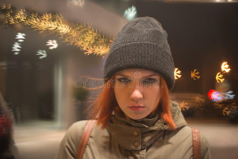 Den unga härliga flickan fångar en taxi i stadsgatan på natten royaltyfria foton