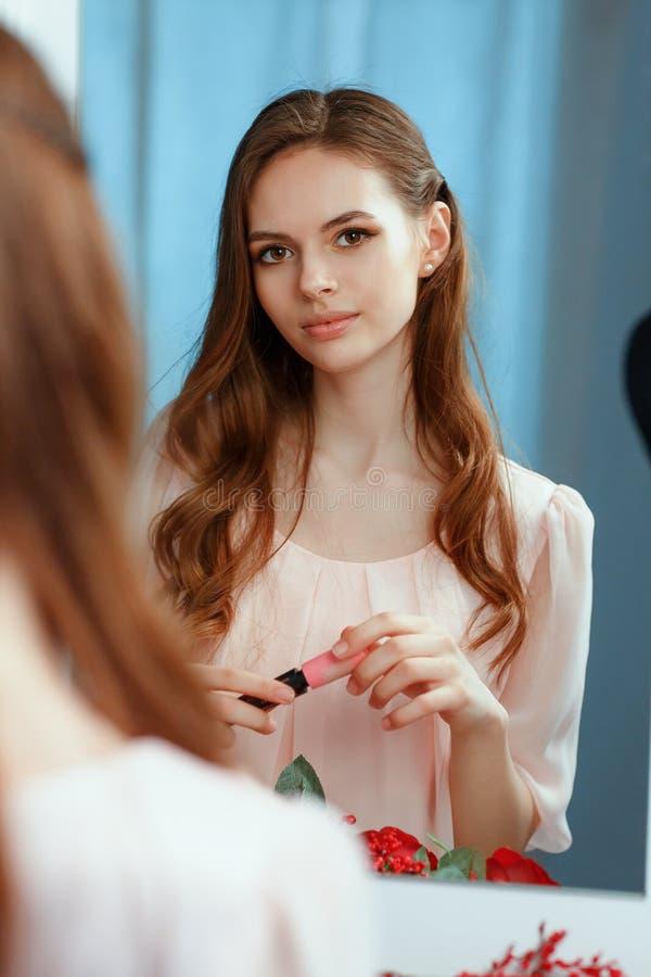 Den unga härliga flickan gör sig en makeup främst av en spegel royaltyfri bild