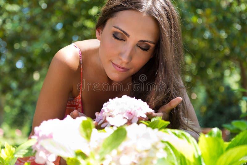Den unga härliga flickan luktar blommor, mot grön sommarträdgård fotografering för bildbyråer