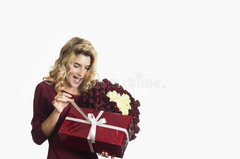 Den unga härliga flickan med en röd gåva med en vit pilbåge och blommor i hennes händer jublar på en isolerad vit bakgrund valent arkivfoto