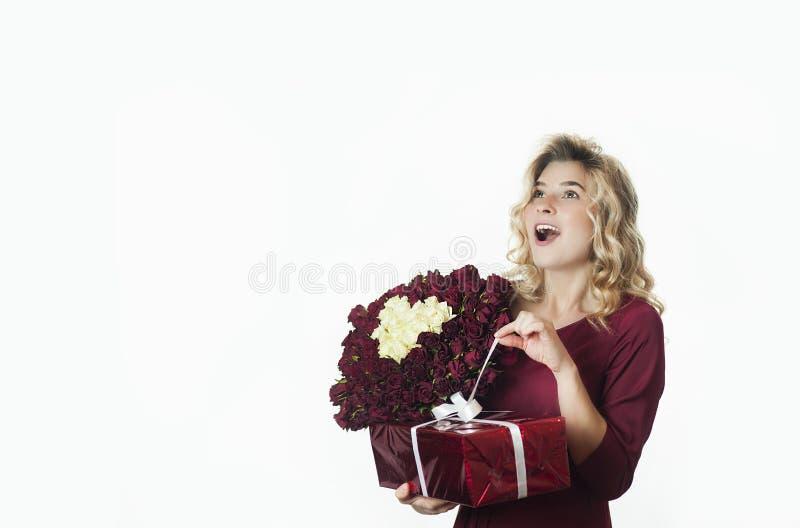 Den unga härliga flickan med en röd gåva med en vit pilbåge och blommor i hennes händer jublar på en isolerad vit bakgrund valent arkivfoton