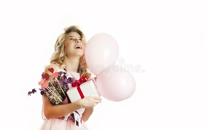 Den unga härliga flickan med en vit gåva med en röd pilbåge, blommor och bollar i hennes händer jublar på en isolerad vit bakgrun arkivfoto