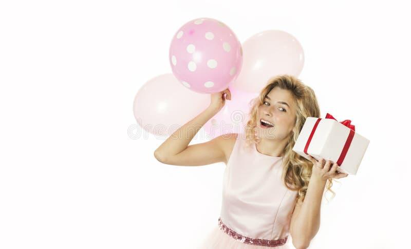 Den unga härliga flickan med en vit gåva med en röd pilbåge och bollar i händerna jublar på en isolerad vit bakgrund valentin fotografering för bildbyråer