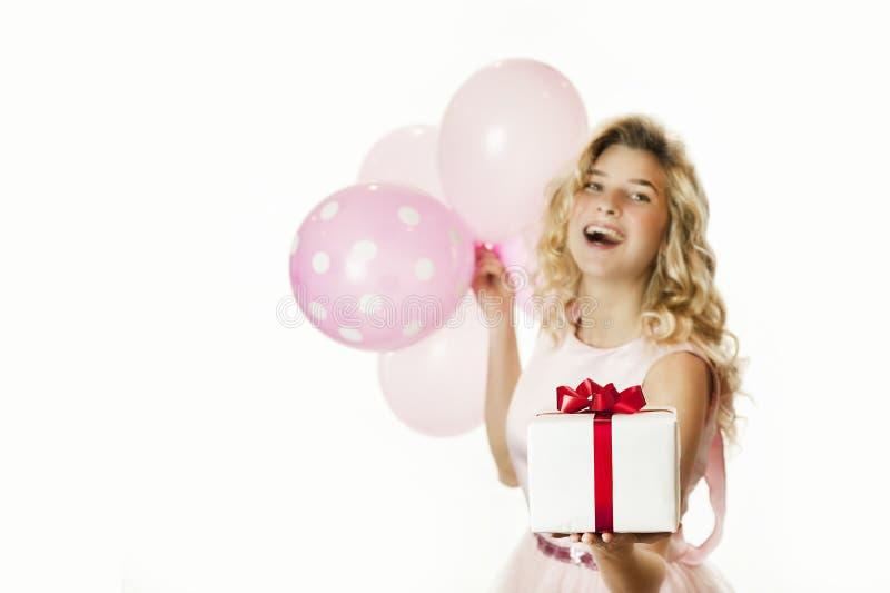 Den unga härliga flickan med en vit gåva med en röd pilbåge och bollar i händerna jublar på en isolerad vit bakgrund valentin arkivfoton