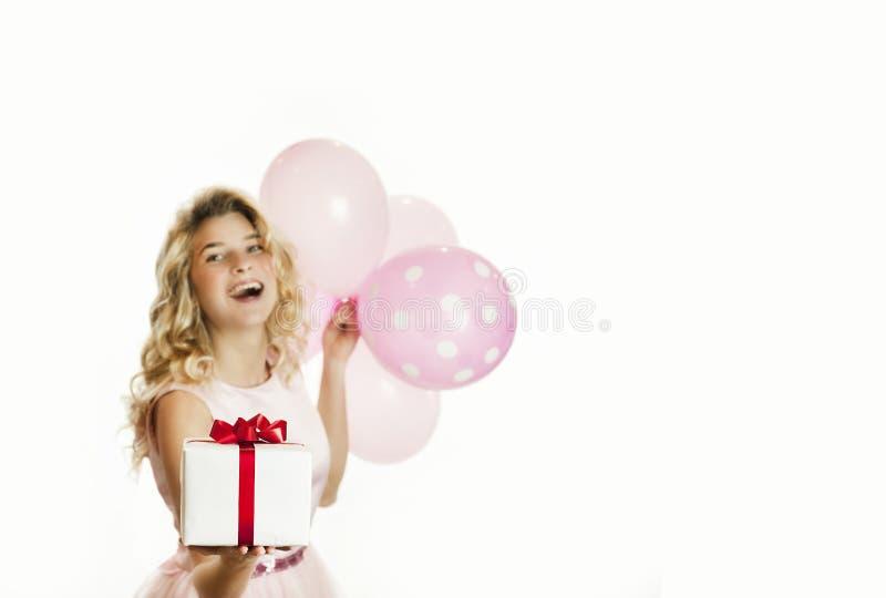 Den unga härliga flickan med en vit gåva med en röd pilbåge och bollar i händerna jublar på en isolerad vit bakgrund valentin arkivfoto