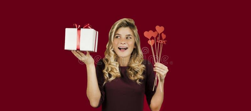 Den unga härliga flickan med en vit gåva med en röd pilbåge och hjärtor i hennes händer jublar på en isolerad röd bakgrund valent arkivbild