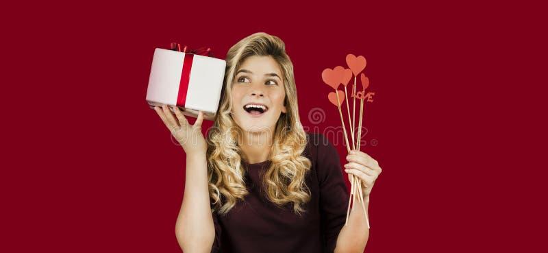 Den unga härliga flickan med en vit gåva med en röd pilbåge och hjärtor i hennes händer jublar på en isolerad röd bakgrund valent arkivfoton