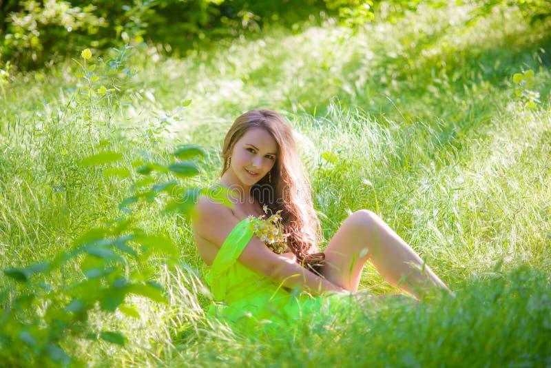 Den unga härliga flickan med långt hår i en ljus klänning arkivfoto