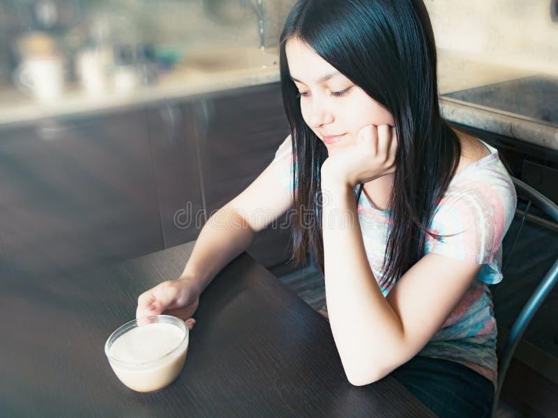 Den unga härliga flickan med mörkt långt hår sitter på en tabell med en kopp kaffe och drömmar om något arkivbilder