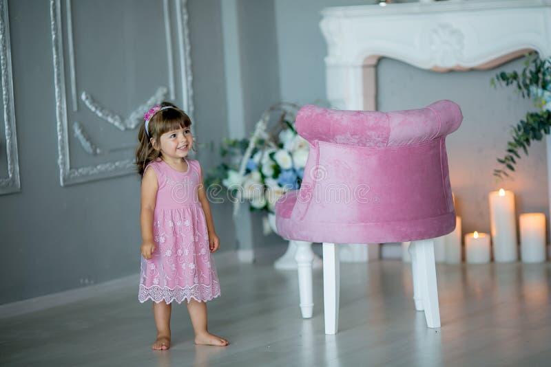 Den unga härliga flickan som ballerina i en vit rosa klänning står i ett vitt rum nära en vit tabell, rymmer en bukett royaltyfri bild