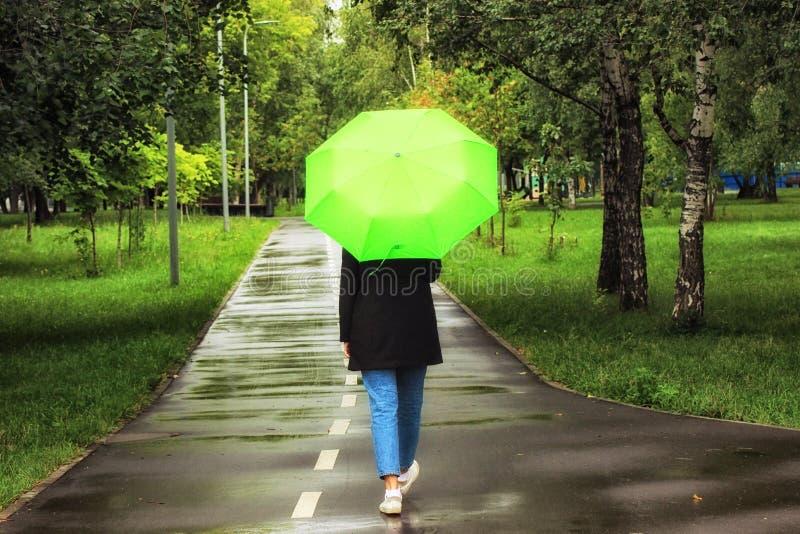 Den unga härliga flickan som bara går under det gröna paraplyet i staden, parkerar i sommartid arkivbild